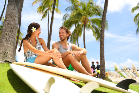 Hawaii surfers people lifestyle happy living couple talking on Waikiki beach relaxing from surfingwith surfboards in Honolulu city. Stock Photo