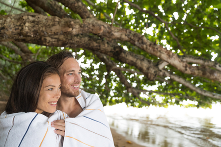 Couple at beach holiday hugging together under towels covering from rain