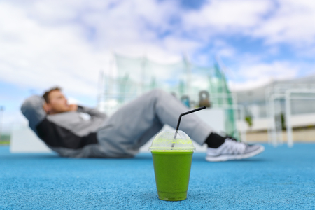 Fitness man training at gym with green smoothie detox drink doing sit-ups exercises on floor outdoors. Stock Photo