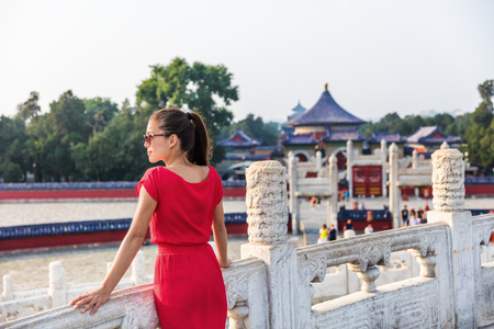 Woman relaxing enjoying scenic view at religious tourist attraction in Beijing, china. Asia travel old temple in summer park.
