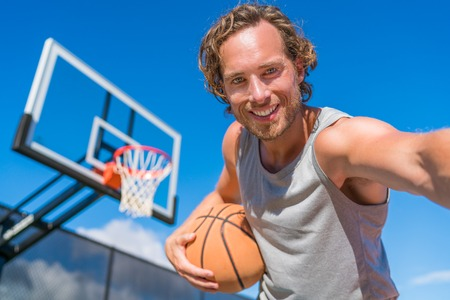 Basketball player man taking fun selfie photo at court net with basket ball. Stock Photo