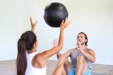 Couple training together at gym. Cross training class at fitness centre, two friends working out throwing medicine ball at each other, partner for motivation.