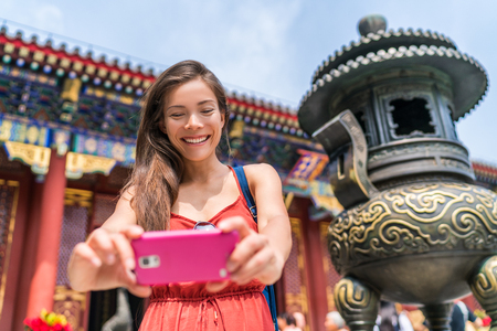 Tourist using mobile phone taking photos of old temple bronze sculpture in Beijing, china. Asia tourism travel. People during vacation. Stock Photo