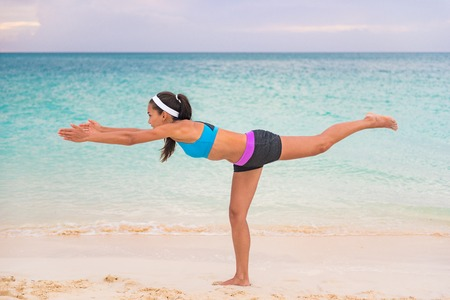 Woman practicing yoga outdoor on beach at sunset. Girl training doing Warrior III pose stretching standing on one leg for balance.