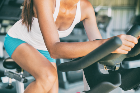 Indoor cycling woman doing HIIT cardio workout biking on indoors gym bike. Girl cyclist working out interval training on bicycle. Closeup of legs and thighs for fat weight loss.