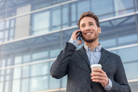Man talking on smartphone. Businessman urban professional business man using mobile phone smiling drinking coffee at office building in city. Happy professional wearing suit jacket. Stock Photo