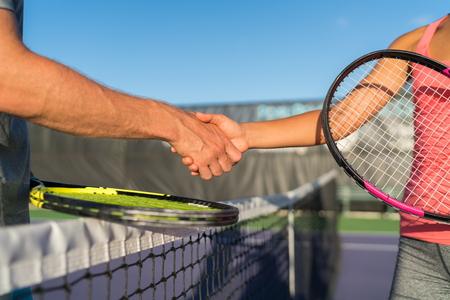 Tennis players shaking hands at court net at end of fun game. Man and woman playing recreational tennis handshaking with tennis racquets. Stock Photo