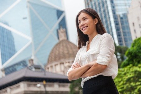 Asian business woman confident in Hong Kong. Businesswoman standing outdoor looking up in hope for future career with city background. Young multiracial Chinese Caucasian professional in Hong Kong.