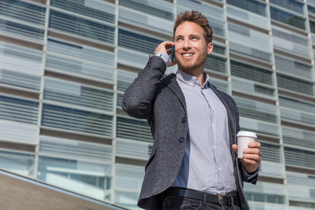 Businessman professional executive talking business on phone. Man in suit jacket calling on smartphone in urban background using smartphone smiling drinking coffee at office building in city.