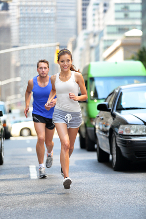 Happy couple runners exercising running outside on street. New York City active lifestyle, joggers athletes training outdoor in traffic.