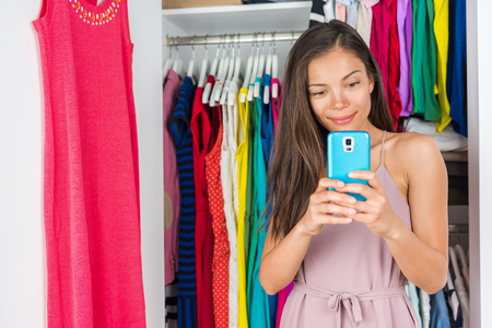 Shopping phone app fashion girl using mobile smartphone to style clothes and choose outfits in closet. Clothes wardrobe young girl taking selfie for styling. Stock Photo