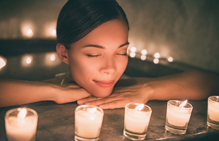 Spa relaxation Asian woman relaxing in hot tub jacuzzi luxury pamper resort. Sleeping girl next to candles, romantic night getaway. Banco de Imagens