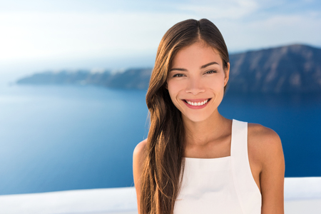 Beautiful Asian young woman smiling portrait in sunshine. Gorgeous Chinese Caucasian model in summer outdoors, Europe travel destination, luxury Santorini Greece getaway. Stock Photo