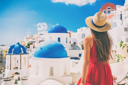 Tourist traveling in Santorini, Oia island in Greece, Europe travel summer vacation woman relaxing at view of three blue domes church famous attraction. holiday girl in hat and red dress enjoying sun.