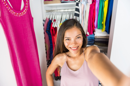Selfie Asian girl taking photo with mobile phone of herself in closet dressing room at home trying on outfit. Clothes fashion style. Shopping girl using smartphone fashion app posting on social media. Stock Photo