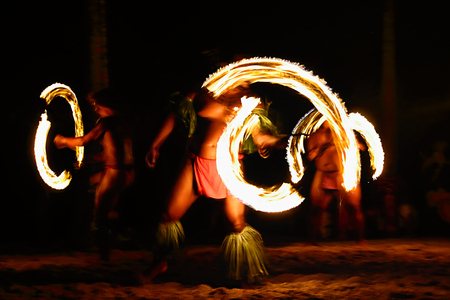 Fire dancers at Hawaii luau show, polynesian hula dance men jugging with fire torches. Stockfoto