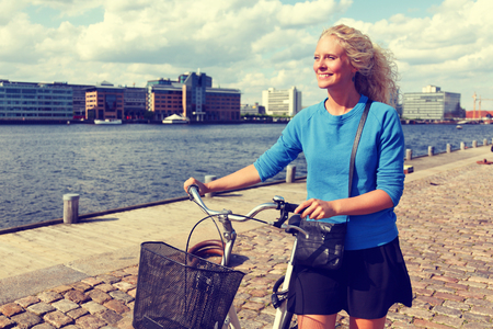 Biking woman with bicycle walking in urban city streets of old harbour. Active healthy lifestyle. Banque d'images