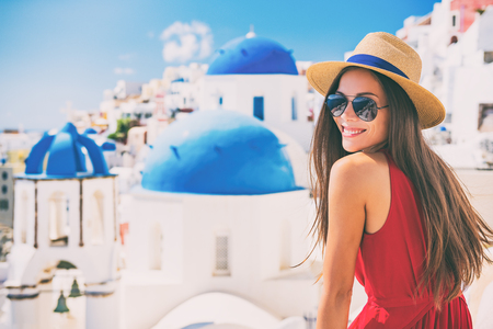 Travel Europe summer holiday girl enjoying Oia, Santorini Greece cruise vacation. Sun getaway Asian woman smiling in hat and sunglasses.