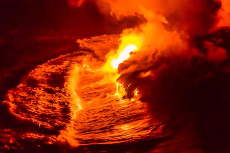 Lavastrom, der nachts in Hawaii-Ozean gießt. Lava, die in Meereswogen in Hawaii vom hawaiischen Kilauea-Vulkan nachts fällt. Geschmolzene Lava wusch sich durch das Pazifische Ozeanwasser, das herein, große Insel, USA zusammenstößt.