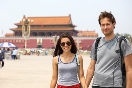 Happy multiracial couple on summer holidays having fun laughing together on Tianamen Square, Beijing, china. Asia travel. Chinese woman, Caucasian man, multiethnic tourists. Stock Photo