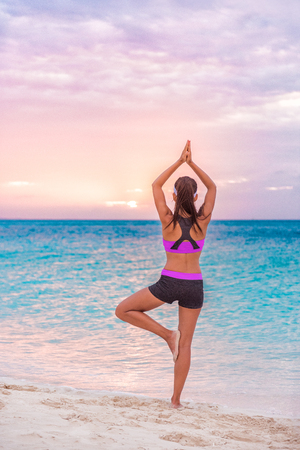 Yoga wellness class on beach at sunset. Girl practicing meditation standing on one leg training balance barefoot on sand enjoying sun and ocean view.