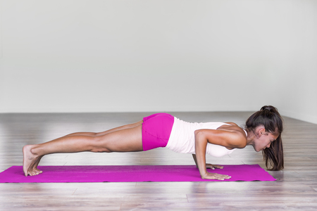 Yoga woman training pushup plank chaturanga dandasana yoga pose girl doing pushups arms and core exercise. Stock Photo