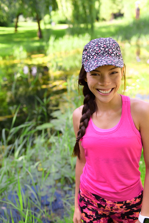 Happy smiling young Asian girl in sportswear sports cap and pink activewear portrait. Chinese Caucasian multiracial runner woman in her 20s in outdoor city park active lifestyle.