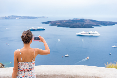 Europe cruise vacation summer travel tourist woman taking picture with phone of Mediterranean Sea in Santorini, Oia, Greece, with cruise ships sailing in ocean background. Stock Photo