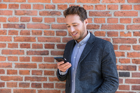 Young business man using smartphone in urban city background relaxing on brick wall texting sms on phone app living a modern lifestyle. Happy businessman playing mobile games.