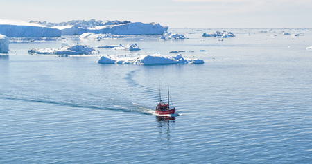 Icebergs and tourist fishing boat in Greenland iceberg landscape of Ilulissat icefjord with giant icebergs. Icebergs from melting glacier. Aerial drone photo of arctic nature. Фото со стока