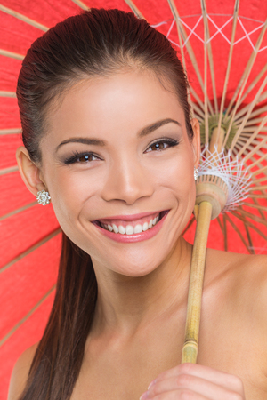 Asian model in studio smiling with paper umbrella sun parasol, Chinese girl smiling, multiracial beauty.