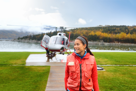 Happy helicopter tourist woman on Alaska tour excursion. Asian girl tourist cruise passenger on shore activity doing helicopter ride in Alaska, USA.