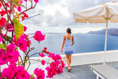 Santorini Oia hotel luxury resort holiday tourist woman looking at view from balcony - Greece summer travel vacation. Фото со стока