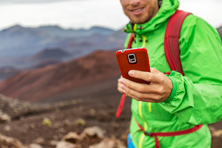 Phone man texting during trek hike in volcano mountain. Young person on travel lifestyle using his smartphone online.