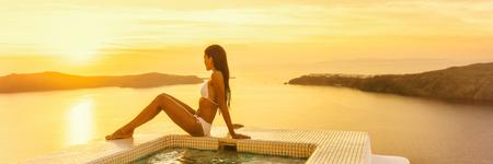 Luxury travel Santorini hotel woman by resort swimming pool at sunset - Bikini body model sunbathing banner panorama.