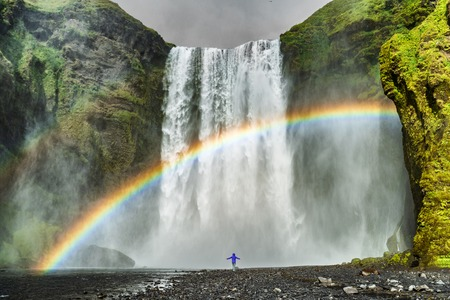 Iceland waterfall travel nature famous tourist destination. Skogafoss waterfall with rainbow and woman under water fall in magical landscape popular Europe attraction.