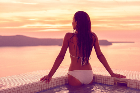 Luxury hotel swimming pool bikini model woman relaxing in jacuzzi spa with Mediterranean sea view at sunset. Girl coming out of water with healthy long hair, body care wellness concept. Zdjęcie Seryjne