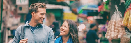 Tourists in Chinatown street market laughing together banner panorama portrait. Asia travel adventure, two people walking visiting Hong Kong. Young woman, man in love. Stock Photo