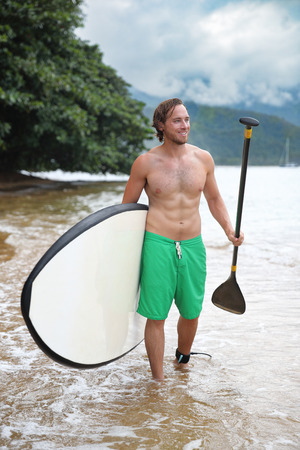 Stand-up paddle board watersport man going paddleboarding on nature lake. Happy fit male athlete with sexy abs body doing swimming activity in summer outdoors.