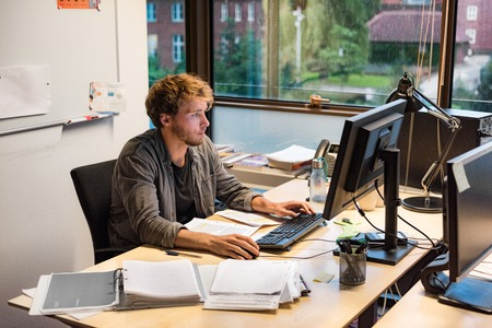 Young phd student studying writing final paper for exam at university. Working man at office desk typing at desktop computer in library room. Stock Photo