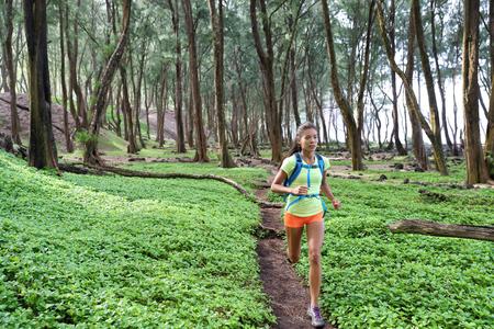 Trail ultra running sport runner athlete woman sprinting in forest green grass. Sport sprinter active doing intense cardio training outdoors in summer landscape.