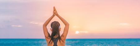 Yoga meditation woman meditating at beach sunset relaxing in yoga tree pose doing sun salutation. Relaxing serene woman enjoying sunshine banner panorama.