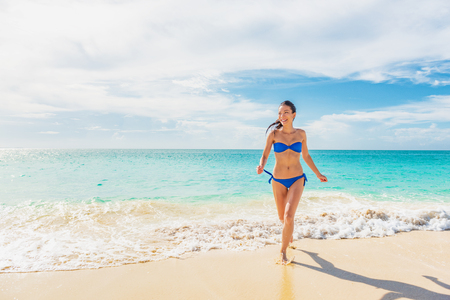 Vacation summer beach bikini girl lifestyle happy woman running out of blue ocean water swimming in tropical Caribbean holiday travel destination.