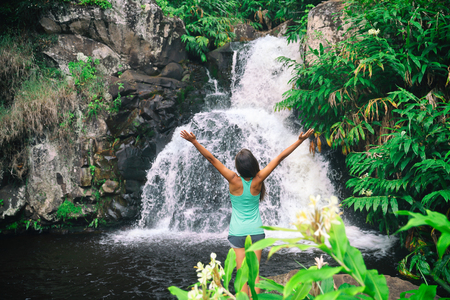 Hawaii travel nature waterfall woman hiker at Canyon Trail Waipoo Falls in Waimea, Kauai island, USA. Freedom happy girl with open arms meditating yoga in rainforest. Stock Photo