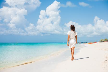 Caribbean beach luxury vacation summer holiday woman walking on perfect white sand tourist destination.