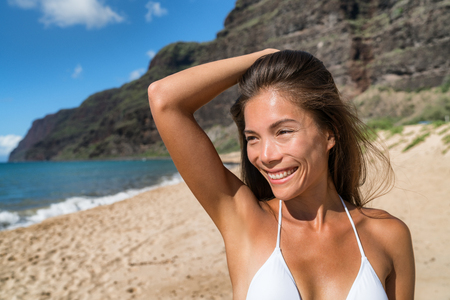 Beach summer vacation lifestyle young Asian woman relaxing sun tan on Hawaii beach. Happy smiling Chinese Caucasian multiracial girl, natural beauty in bikini portrait. Stock Photo