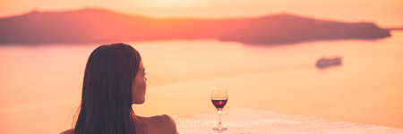 Luxury travel woman drinking red wine glass watching sunset on cruise ship holiday vacation - rich people high end lifestyle banner panorama landscape.