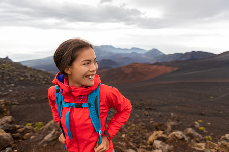 Hiking Asian woman in outdoor volcano landscape walking in Hawaii. Happy hiker on trek with backpack and red rain jacket.
