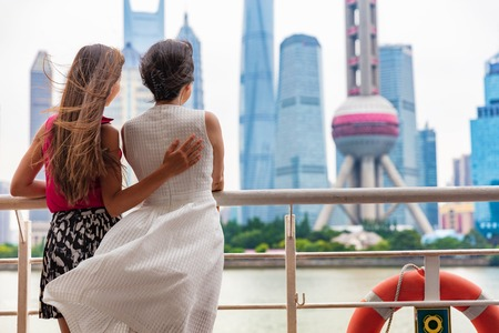Two women taking the ferry in Shanghai city, China, crossing the Bund river looking at the view of famous pearl tv tower, landmark. Travel people lifestyle.