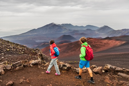 Hawaii volcano hikers people walking hiking on mountains in Haleakala volcanic background landscape. Two young tourists couple on trek hike outdoors. Stock Photo